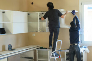 Two handymen installing white cabinet.