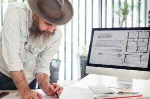 Beard man in white sleeve sketching a floor plan.