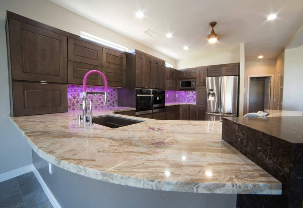 Marble table and dark brown cabinets.